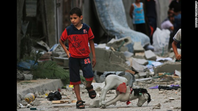 A Palestinian child walks on debris from a destroyed house, following an overnight Israeli strike in Beit Lahiya, in northern Gaza strip, Saturday, July 19, 2014. A Gaza health official says the death toll from Israel's 12-day offensive against Hamas militants has topped 300. (AP Photo/Lefteris Pitarakis)