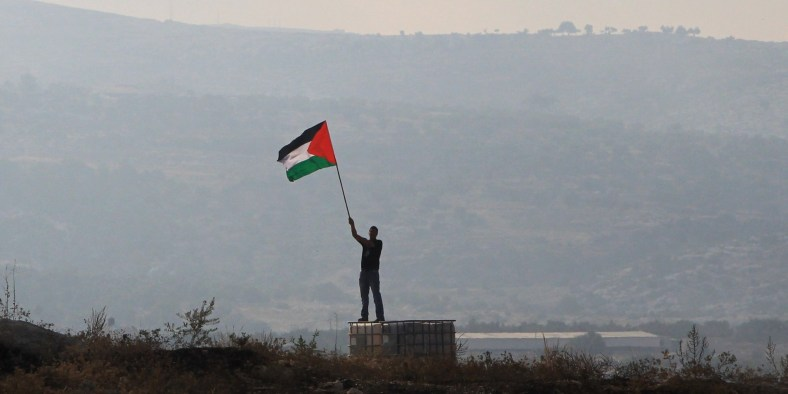 A Palestinian protester holds his national flag during clashes with Israeli security forces (unseen) in the West Bank village of Bilin, on July 28, 2014, following a demonstration in support of Palestinians from the Gaza Strip. The protesters performed the Eid al-Fitr prayer in front of the Israeli built controversial separation barrier, protesting against the ongoing Israeli military offensive in the Palestinian enclave.  The Muslim three-day Eid al-Fitr festival, that marks the end of the fasting month of Ramadan, began notably in Saudi Arabia, Egypt, Palestinian territories, Kuwait, Lebanon, Qatar, Syria or Yemen, where reports of sightings of the new moon were received. AFP PHOTO / ABBAS MOMANI        (Photo credit should read ABBAS MOMANI/AFP/Getty Images)