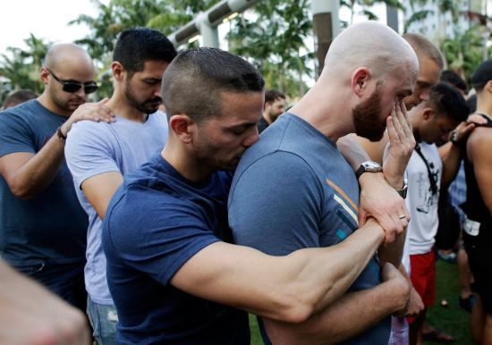 Caleb McGrew, right, wipes tears as he stands with his partner Yosniel Delgado Giniebra, center, during a vigil in memory of the victims of the Orlando mass shooting, Sunday, June 12, 2016, in Miami Beach, Fla. A gunman opened fire inside a crowded gay nightclub early Sunday, before dying in a gunfight with SWAT officers, police said. (AP Photo/Lynne Sladky)